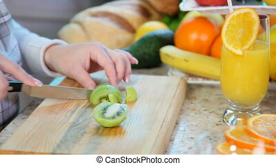 women hands slicing kiwi