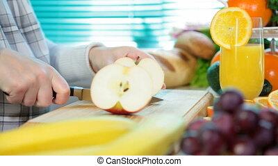 Women hands slicing red apple