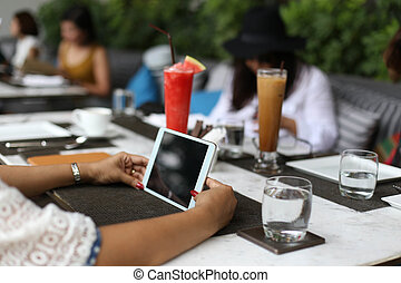 women hands with tablet computer and juice dink