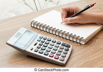 Women hands writing with pencil, notebook and Calculator