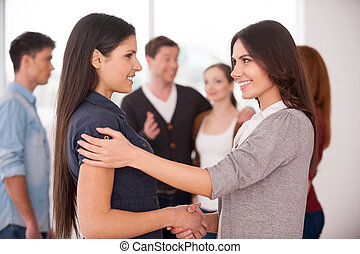 Women handshaking. Two cheerful young women handshaking while group of people communicating on background