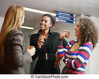 women having coffee break - group of multiethnic female...