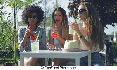 Women having drinks in summer day - Group of three young...