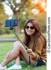 women hold monopod use smart phone take photograph selfie in...