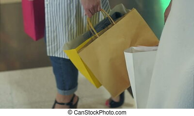 Women holding shopping bags in hands, walking after shopping in mall