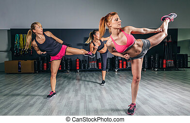 Women in a boxing class training high kick - Group of...