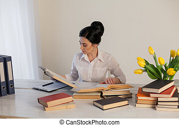 women in a business suit behind a table with books