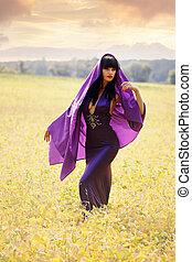 women in a purple cloak in field