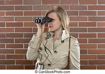 women in a trenchcoat with binoculars