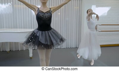 Women in black and white ballet tutu gently move their hands...