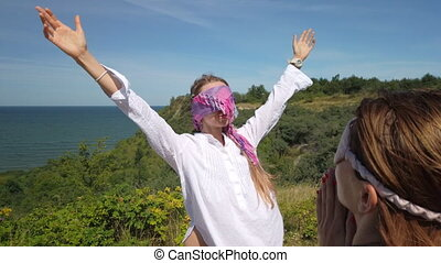 Pan around view of female friends in blindfolds standing on cliff against sea and enjoying freedom