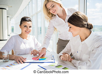 Women in business - Three confident office workers sitting ...