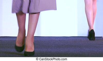 Women in dresses show attire on the podium