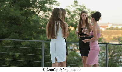 Women in evening dresses drinking champagne and talking on...