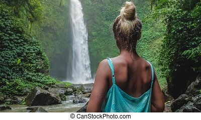 Women in front of tropical waterfall surrounded by lush...