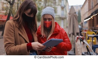 Attractive young women in warm clothing and face masks standing on street and holding digital tablet. Concept of friendship during quarantine.