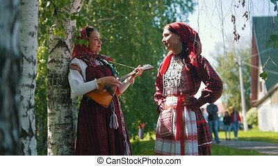Women in national Russian costumes stand near birch one of...
