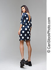 Women in short polka dot dress back playfully look