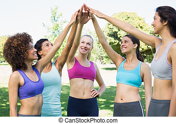 Women in sportswear raising hands i - Happy young women in ...