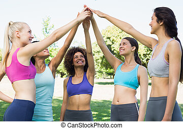 Women in sportswear raising hands in park - Happy young...