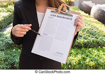 Women in suit showing car insurance policy and pointing with a pencil