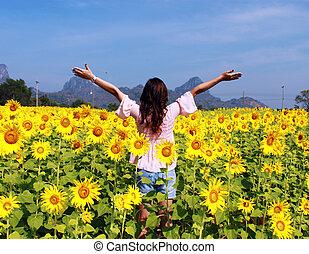 Women in the field of sunflowers