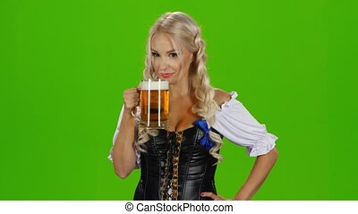 Women in traditional bavarian tracht drinking beer and showing thumbs up. Green screen
