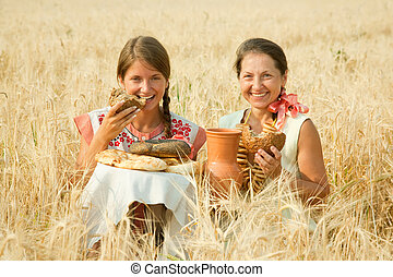 Women in traditional clothes with bread