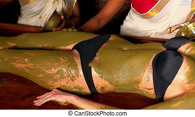 Women Indian beautician applied therapeutic clay of natural  to patient's body.