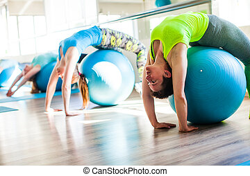 Women involved in Pilates - Pilates stretching training. ...