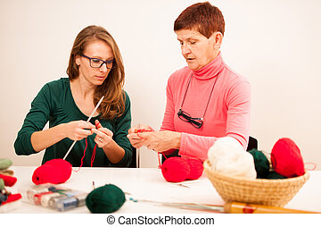 Women knitting with red wool. Eldery woman transfering her knowledge of knitting on a younger woman on handcraft workshop.