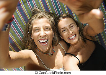 Women laughing in hammock.