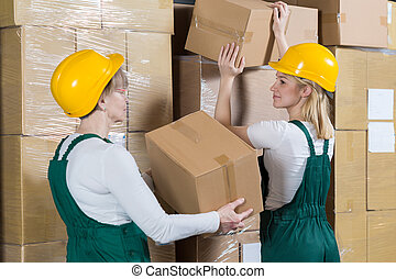 Women laying the boxes - Two hardworking women laying the...