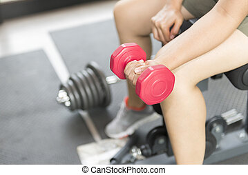 women lift the dumbbell for exercise.The hand hold the red...