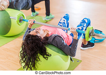 Women lifting barbell lying on stability ball while exercising in gym