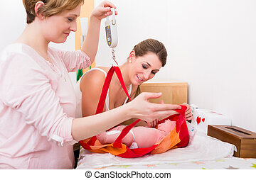 Women looking at baby in the weighing bag