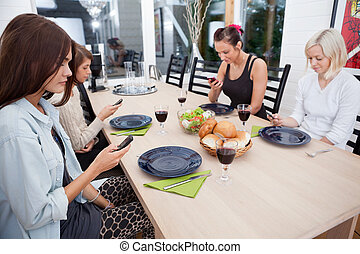 Women looking at cell phones - Female friends sitting at...