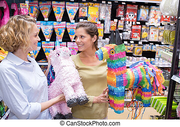 women looking at pinatas in novelty gift store