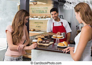 Women looking at sweet food at coffee shop - Young women...