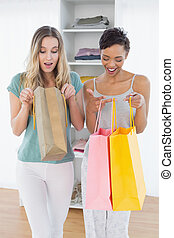 Women looking into shopping bags at home