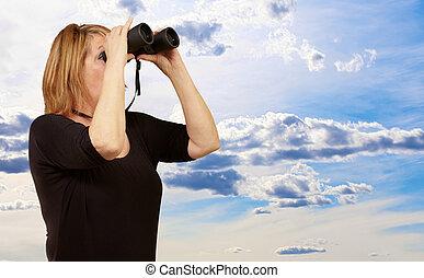 Women looking through binoculars, outdoor