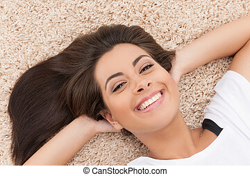 Women lying on the floor. Top view of cheerful young women...