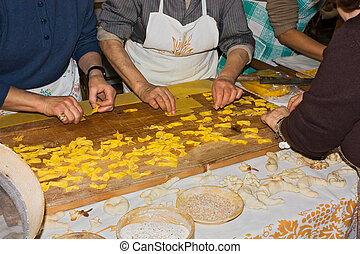 women making pasta - FORLI', ITALY - JANUARY 30: traditional...