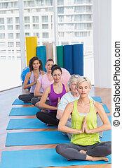 Women meditating in fitness class