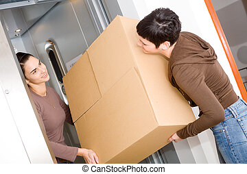 Two happy women moving cardboard box with elevator, smiling.