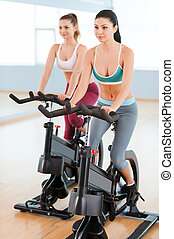 Women on exercise bikes. Two beautiful young women in sports clothing exercising on gym bicycles