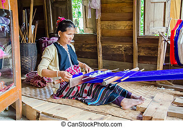 Women Pa-Ka-Geh-Yor (Karen Sgaw) in Tribal dress was weaving. Ethnic group spread north of Thailand. Image is taken at Doi Inthanon, Chiang Mai, Thailand.