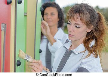 Women painting outdoor play equipment