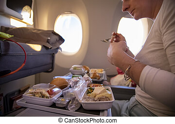 women passenger of aircraft seats in seat and eats tasty hot inflight meal on a folding table. in the background is a window in the porthole. side view