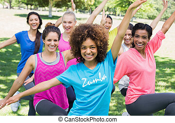 Women performing fitness dance in park - Portrait of smiling...